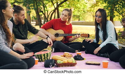 Romantic young people are singing and playing the guitar on...