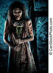Pretty woman zombie standing at the night cemetery and tenderly holding a flower.