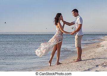 romantico, colpo, di, giovane coppia, spiaggia, durante, sunset., lungo, vestire
