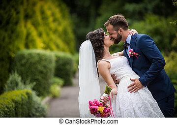 romantikus, fairytale, boldog, newlywed, összekapcsol dédelget, és, csókolózás, alatt, egy, liget, bitófák, alatt, háttér
