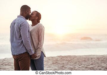 romantisch paar, jonge, ondergaande zon , afrikaan, kussende , strand