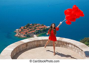 romantische, meisje, in, rode jurk, op, sveti, stefan, eiland, in, budva, montenegro., vrolijke , brunette, reiziger, met, hartjes, ballons, sightseeing, adriatische zee, balkans., zomer, reizen, vakantie, achtergrond.