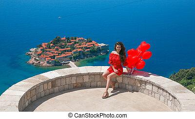 romantische, meisje, in, rode jurk, sightseeing, sveti, stefan, eiland, in, budva, montenegro., vrolijke , brunette, reiziger, met, hartjes, ballons, op, adriatische zee, balkans., zomer, reizen, vakantie, achtergrond.