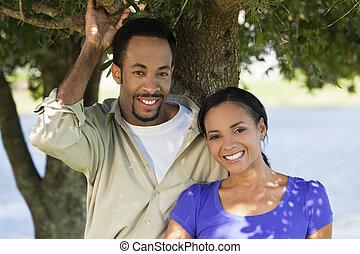 romantyczna para, pod, drzewo, amerykanka, afrykanin, uśmiechnięty szczęśliwy
