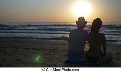 romantyk, posiedzenie, para przygarniająca, całowanie, plaża, wschód słońca
