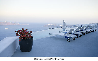 Roof garden of a holiday resort hotel against the ocean at sunset. Oia village, Santorini Island, Greece.