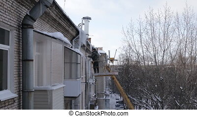Roof icicle removal in winter day