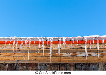 Roof, icicles and blue sky - Icicles hang from a rooftop...