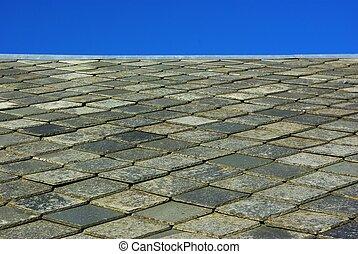 Roof made of plates of slate on blue sky