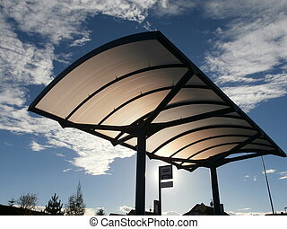 Roof of bus stop lit by evening sun