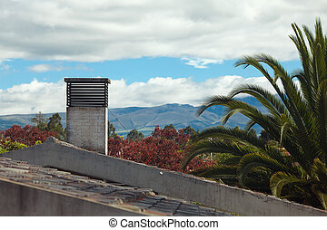 roof of the house and a palm tree on a background of mountains