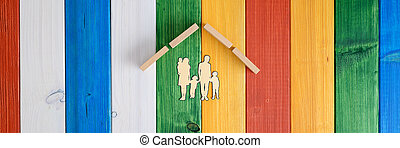 Roof over a paper cut silhouette of a family in a conceptual image