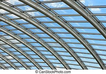 Silver metal curved roof joists in a conservatory with glass panes in between and a blue sky and clouds beyond.