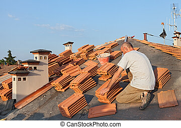 roof tile installation - roofing: construction worker on a...