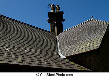 A slate roof with chimney and ridge tiles and a lead valley with green lichen and moss leading off.