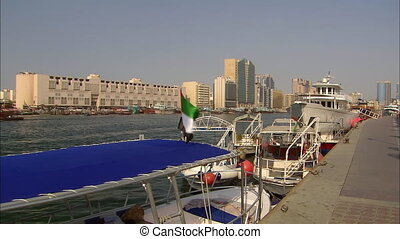 Wide low-angle panoramic still shot of roofed sailing boats docked at a pier in dark grey beach water, traditional and modern buildings along the beach, Dubai Creek, UAE