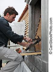 Roofer adjusting slate tile