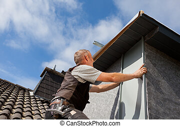 Roofer assembles a metal piece into the dormer wall on a sunny day