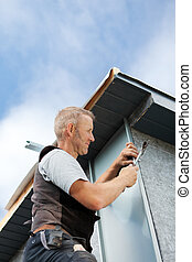 Roofer assembling a metal piece into the dormer wall on a...