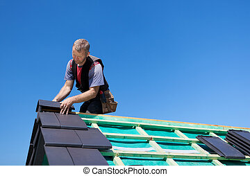 Roofer assembling edged tiles to the roof