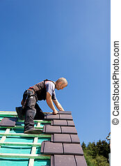 Roofer assembling gray tiles over the beams on a sunny day