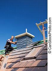 Roofer assembling tiles on a chimney