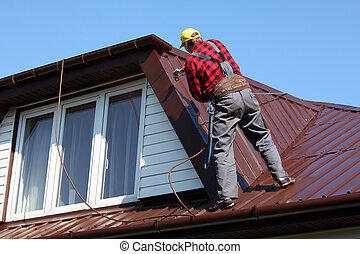 roofer builder worker with pulverizer spraying paint on...