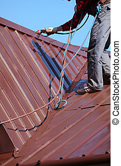 roofer builder worker with pulverizer spraying paint on roof