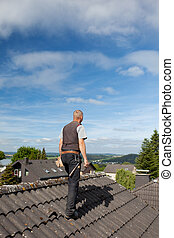 Roofer carrying tools on the rooftop