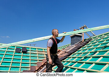 Roofer climbing the roof with a beam
