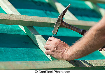 Roofer hammering a nail on the roof beams