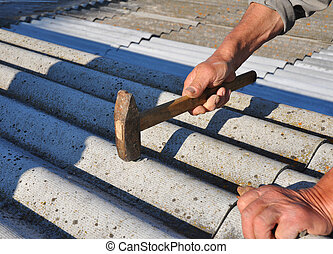 Roofer hammering nail in asbestos old roof tiles. Roofing construction