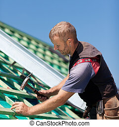 Roofer hammering nails into roof beams for the construction of the roof