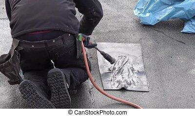 Roofer installing chimney using bitumen and gas flame -...
