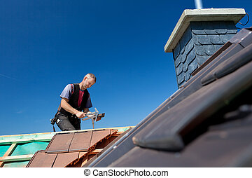 Roofer molding tiles with a hammer - Roofer molding tiles...