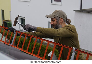 Roofer or a worker repaired on the roof snow guard grating