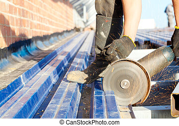 Roofer sawing roofing steel sheet - Construction worker...