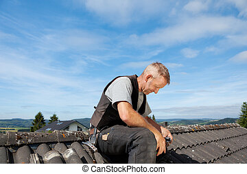 Roofer sitting on the rooftop