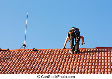 Roofer finishing laying the tiles on the roof of a building