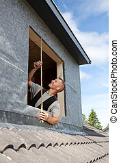 Roofer taking measures for a new window - Roofer taking ...