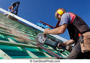 Roofer using a hand circular saw to cut a roof-tile