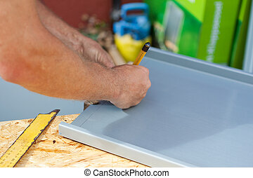 Roofer using a pencil to make markings on a metal sheet