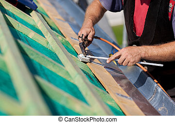 Detail of a roofer welding the gutter on a new roof