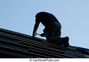 Roofer with Hammer - man on roof with hammer - installing...