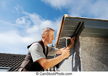 Roofer working on a new dormer by hammering nails into the roof edge