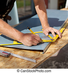 Roofer working with a protractor to make markings on a metal sheet