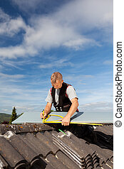 Roofer working with an angle ruler on a rooftop
