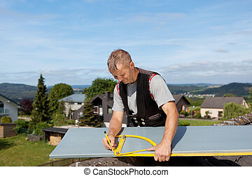 Roofer working with an angle ruler to mark a metal sheet