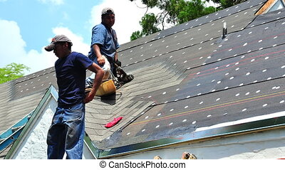 Roofing - Time lapse of three roofers working on the roof of...