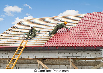roofing work with metal tile - two workers on roof at works...